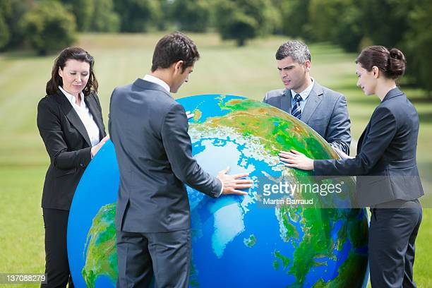 Business people standing with large ball outdoors