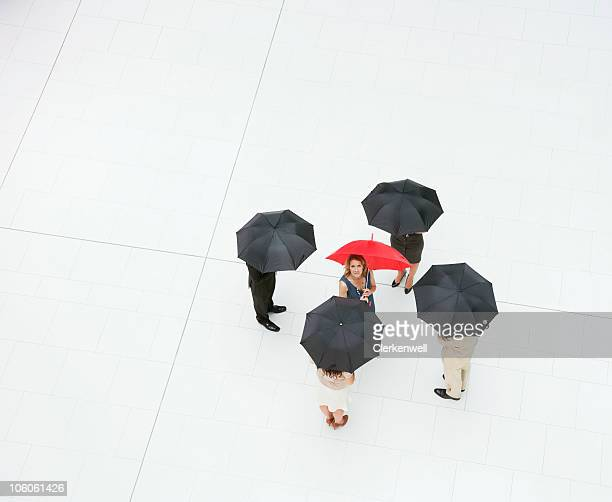 Business people standing with umbrellas while one of them looks up
