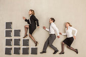 Business people stepping on staircase of files