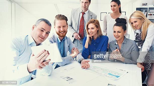 Business people taking selfies.