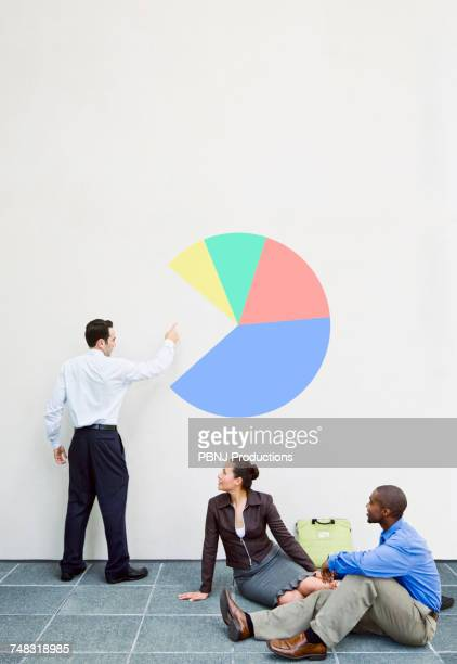Business people talking about chart on wall