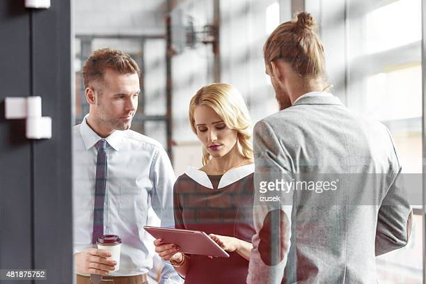 Business people talking in an office, woman holding digital tablet