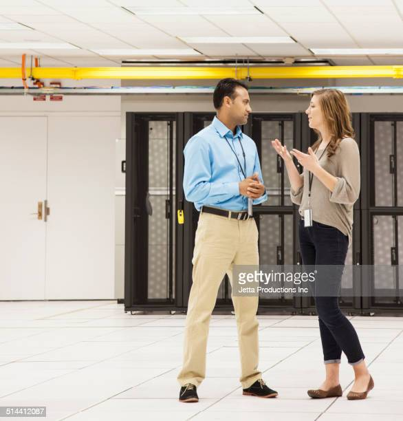 Business people talking in server room