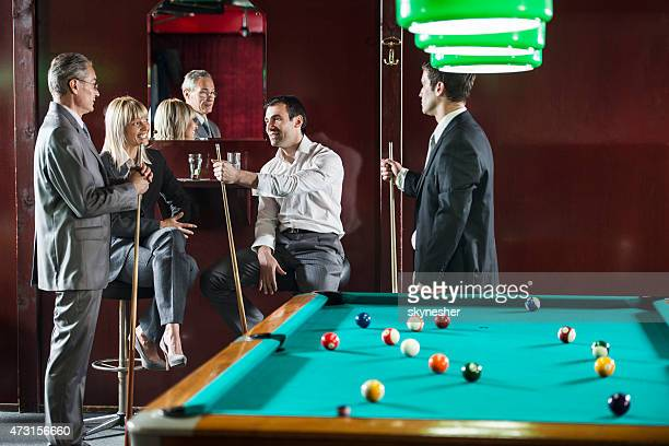 Business people talking in the pub and playing billiard.