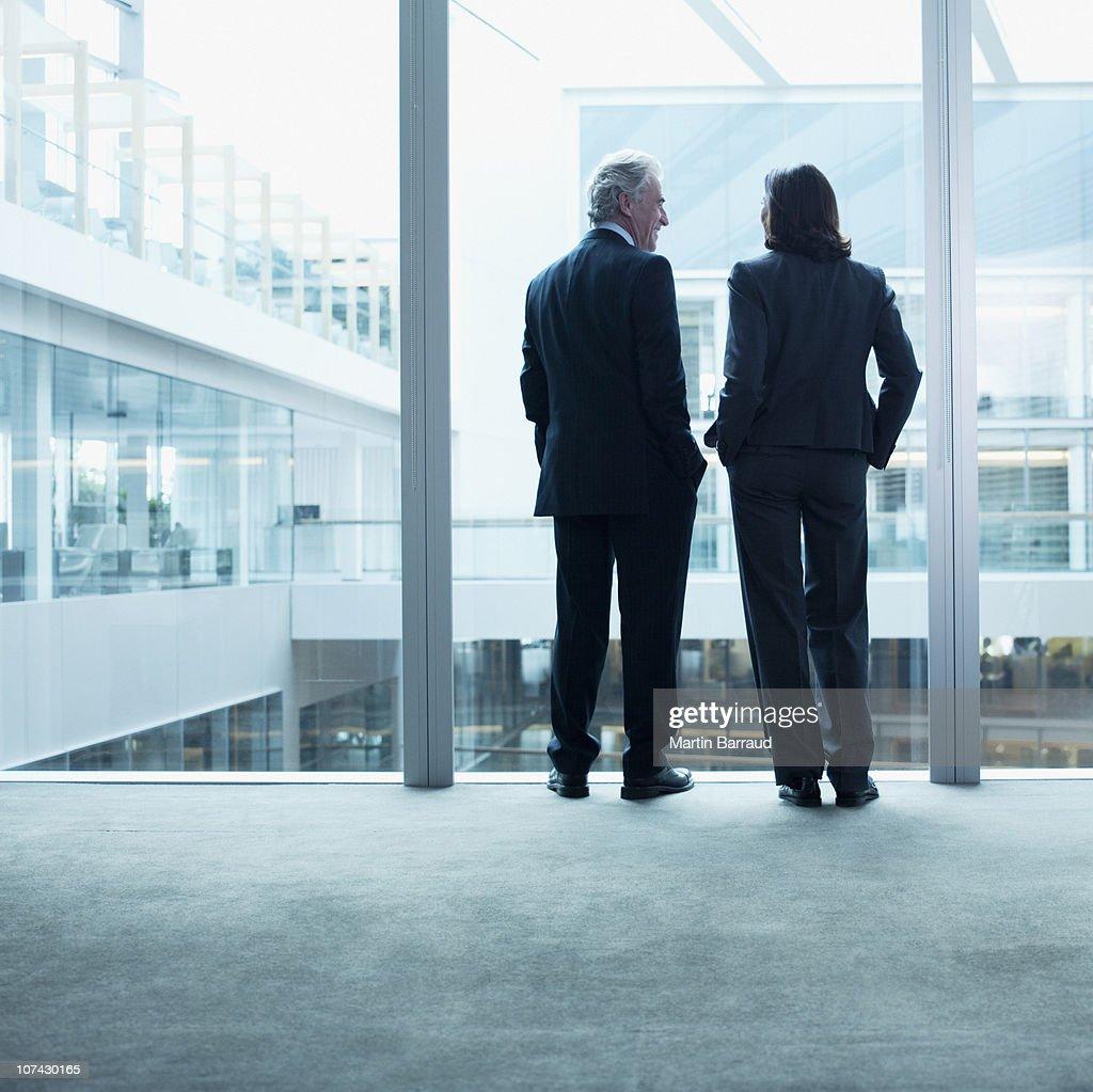 Business people talking near glass wall in office : Stock Photo