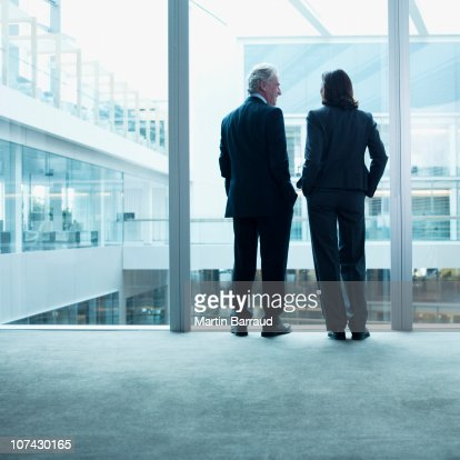 Business people talking near glass wall in office : Stock Photo