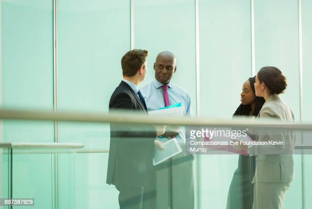 Business people talking on atrium balcony