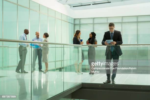 Business people talking on office atrium walkway