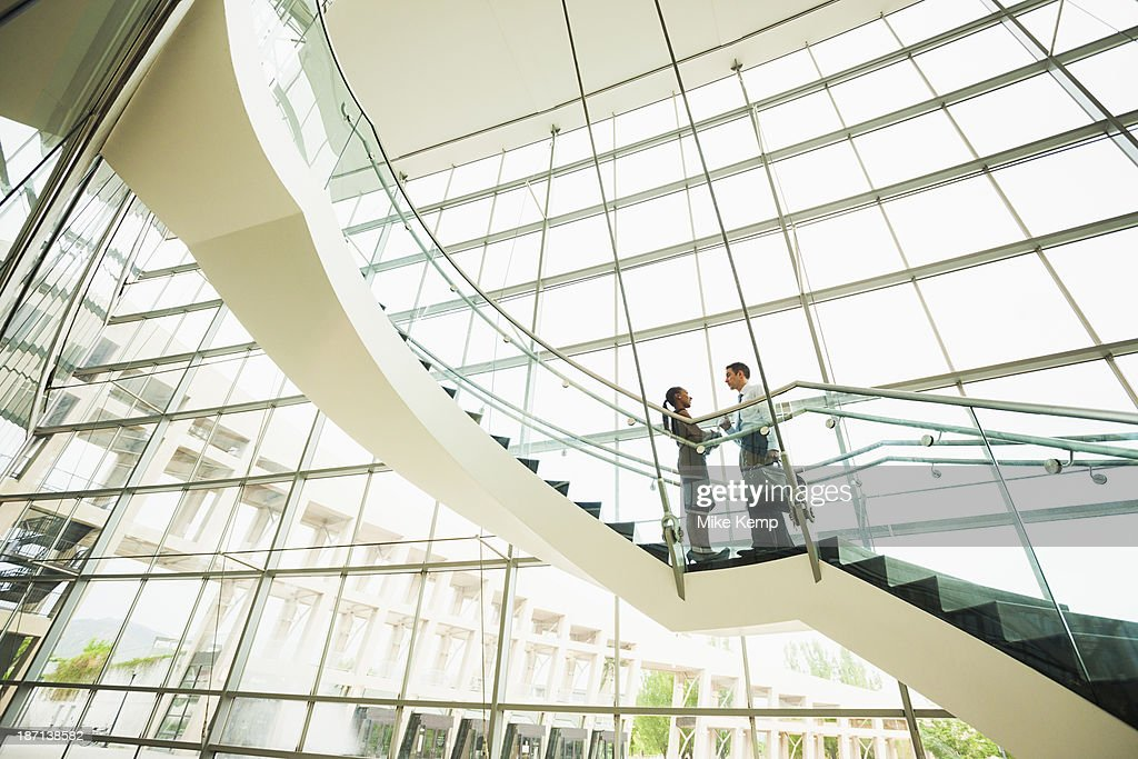 Business people talking on office staircase