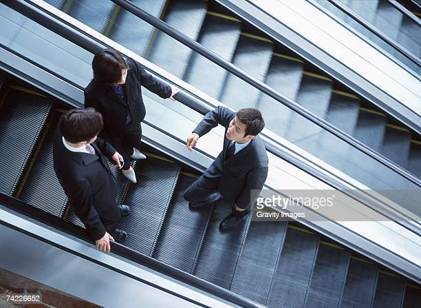 'Business people talking standing on escalator, elevated view'