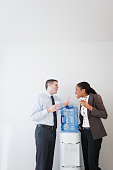 Business people talking together at water cooler