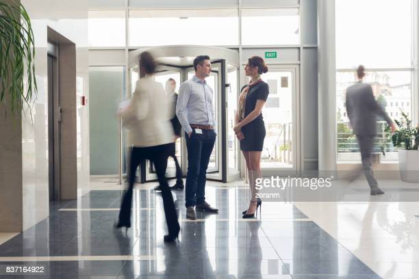 Business people talking while people rushing pass them