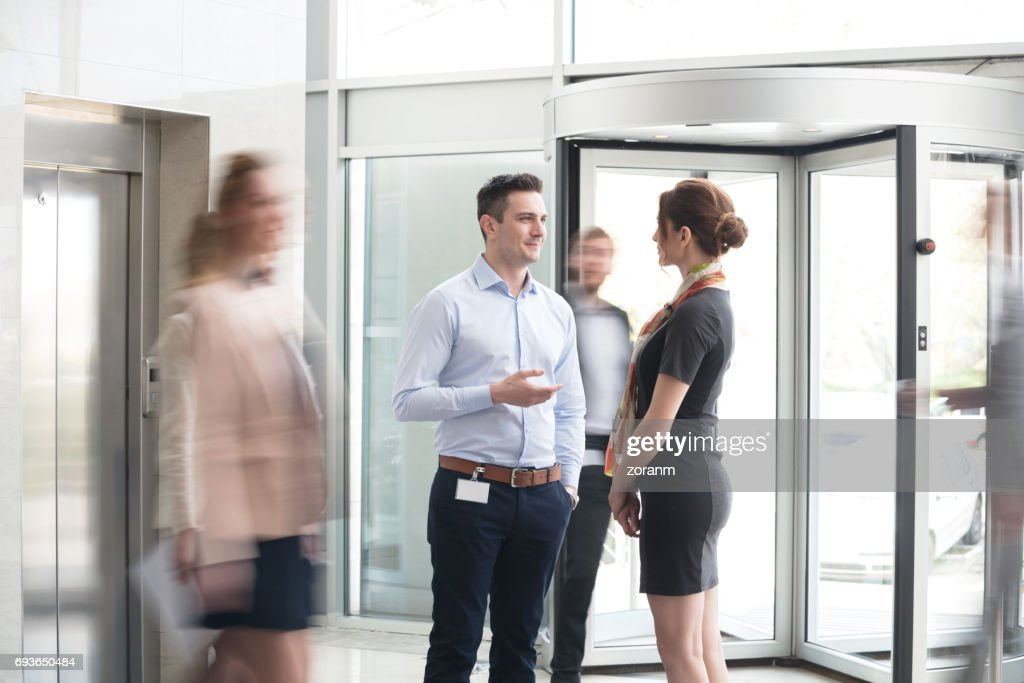 people talking in elevator. business people talking while rushing past them : stock photo in elevator e