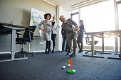 Business people teambuilding in office space with mini golf, laughing looking positive