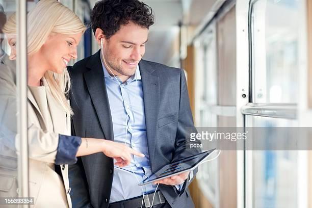 business people travelling on passenger train using digital tablet