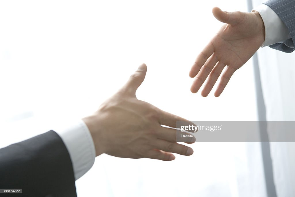 Business people trying to shake hand : Stock Photo