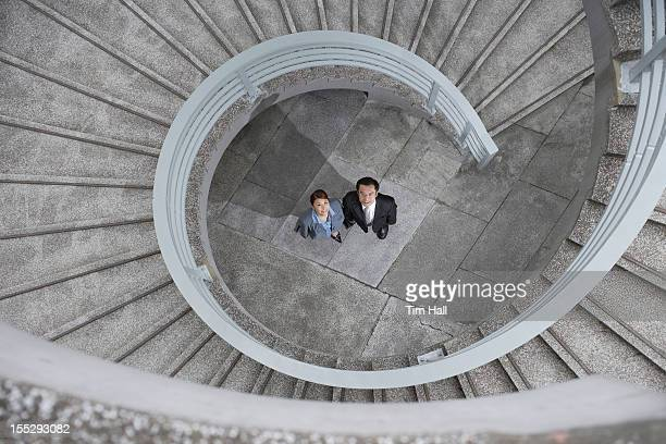 Business people under spiral staircase