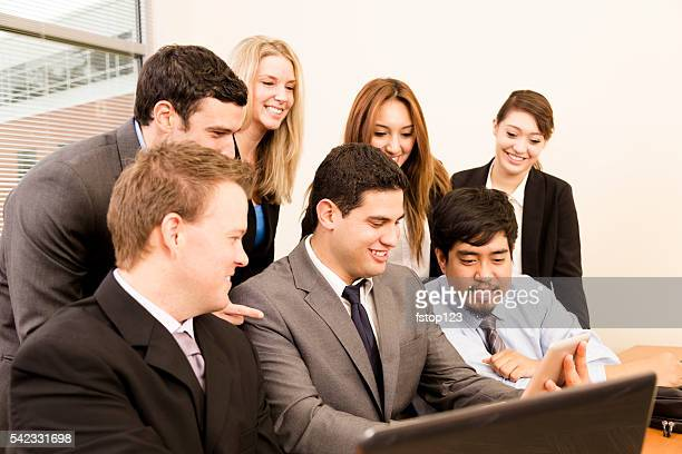Business people use digital tablet, laptop during office meeting.