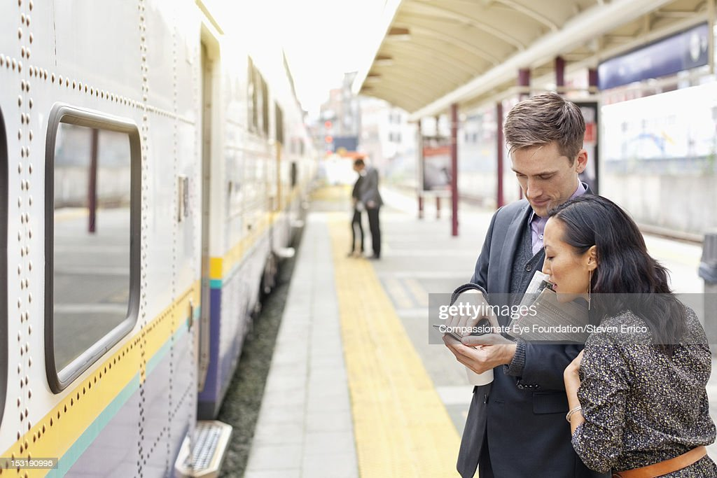 Business people using cell phone at train station
