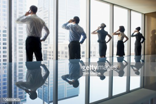 Business people using cell phones in conference room