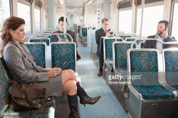 Business people using cell phones on train