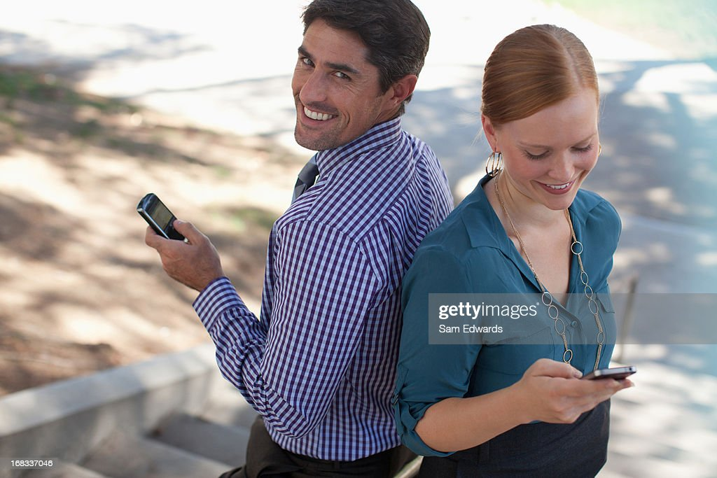 Business people using cell phones outdoors : Stock Photo