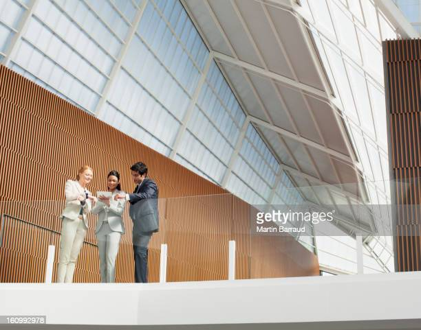 Business people using digital tablet on modern balcony in office