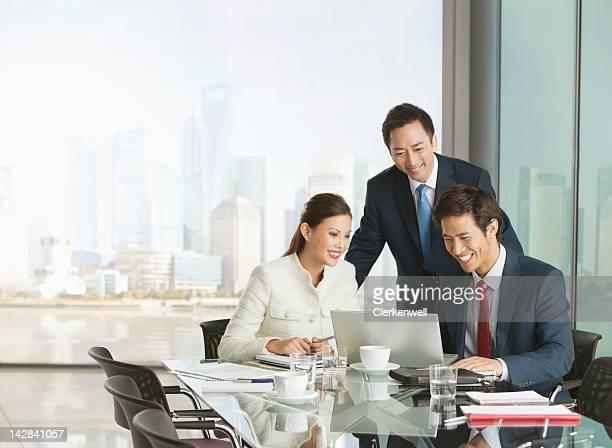 Gente de negocios utilizando el ordenador portátil en la sala de reuniones
