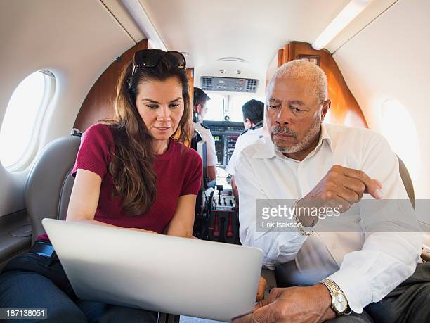 Business people using laptop on airplane