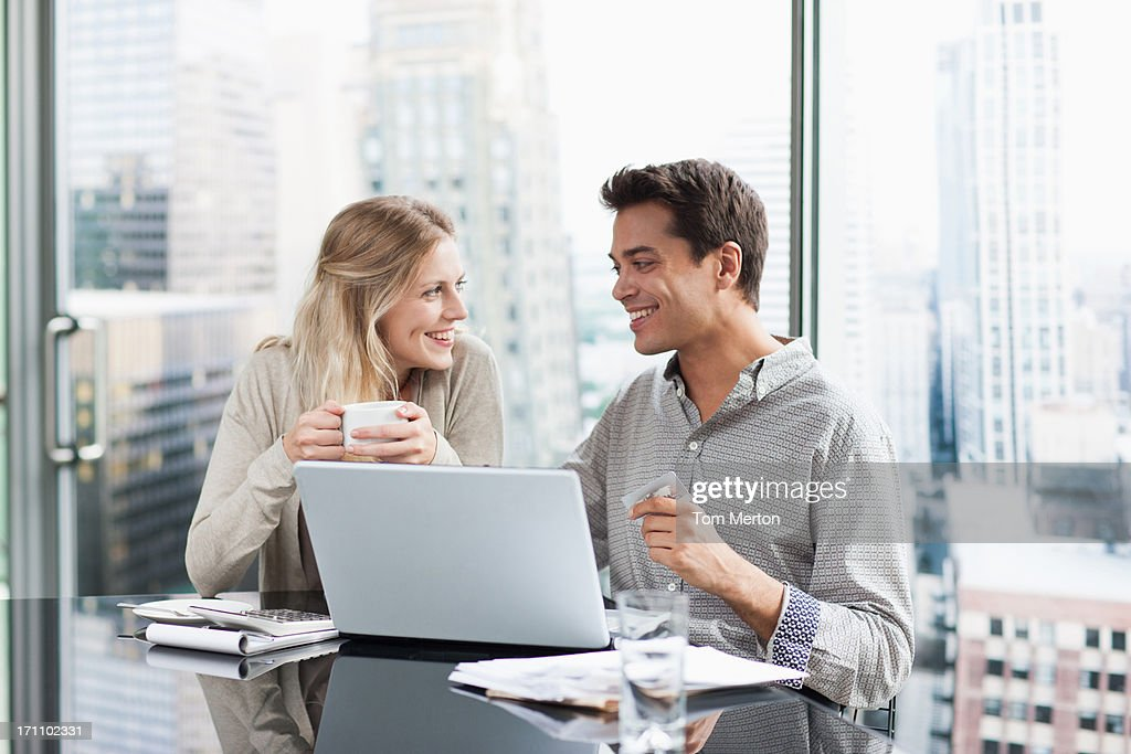 Business people using laptop together : Stock Photo