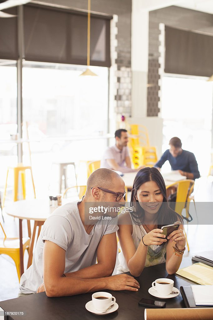 Business people using mobile phone in cafe : Stock Photo
