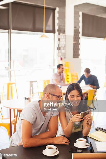 Business people using mobile phone in cafe