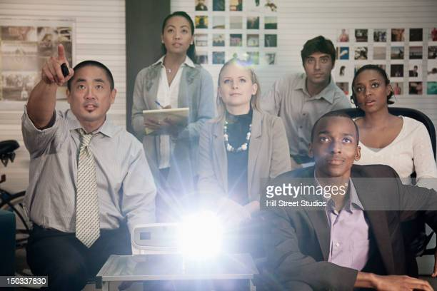 Business people using projector in conference room