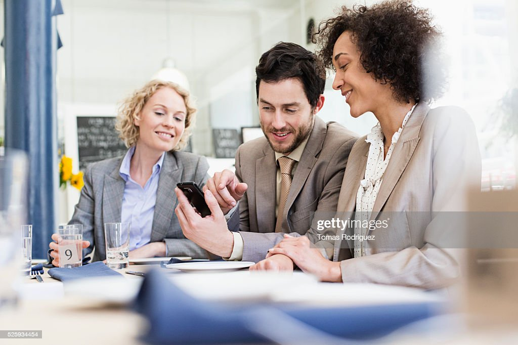 Business people using smartphone in restaurant : Stock Photo