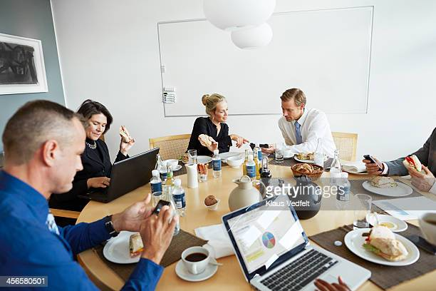 Business people using technology at lunch meeting