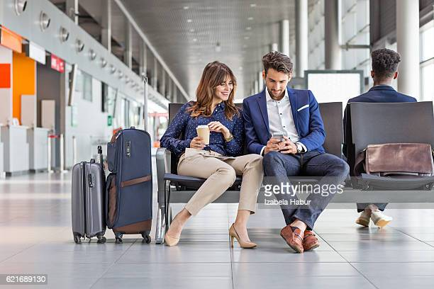 Business people waiting for flight at airport lounge