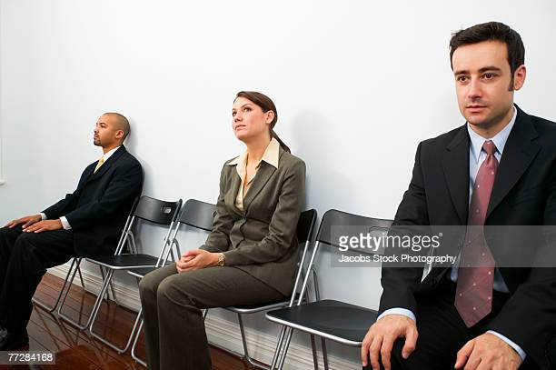 Business people waiting on folding chairs