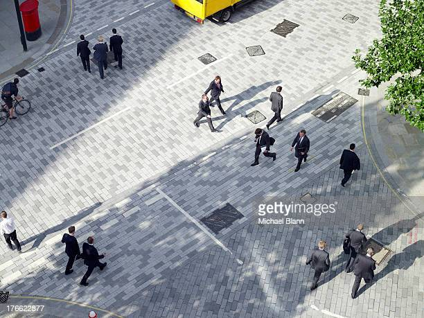 business people walking across a road, aerial view