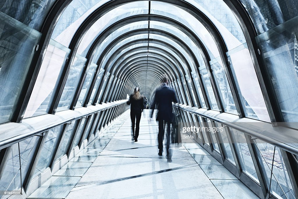 Business people walking along an elevated walkway : Stock Photo