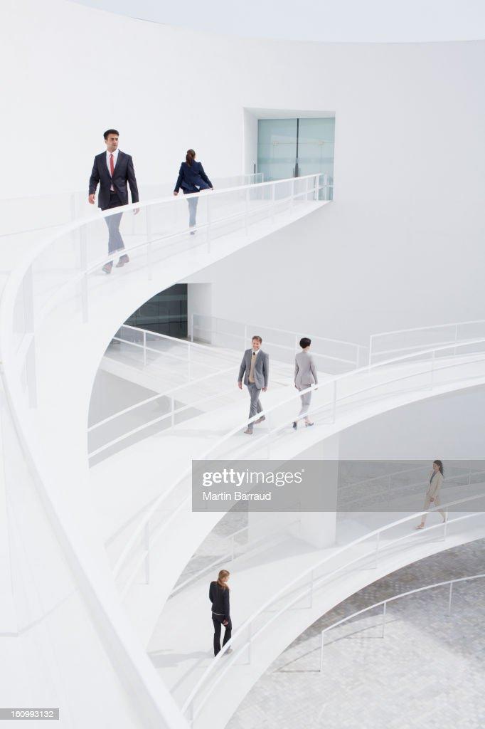 Business people walking along elevated walkways : Stock Photo