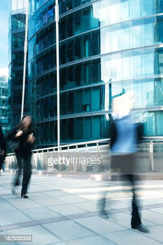 Business people walking along office building, blurred motion