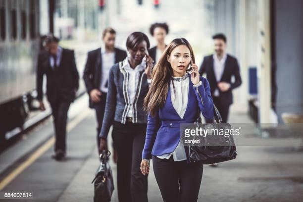 Business People Walking Along Train Station Platform