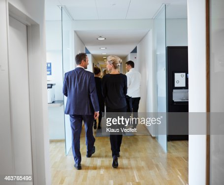 Business people walking and talking down aisle