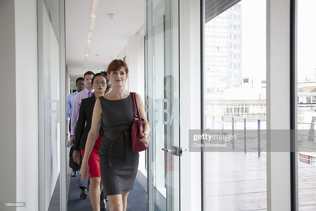 Business people walking down corridor : Stock Photo