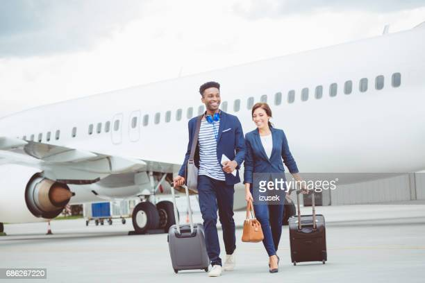 Business people walking in front of the airplane with luggage