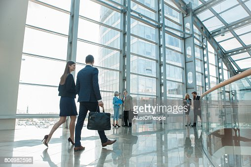 Business people walking in glass building : Stock Photo