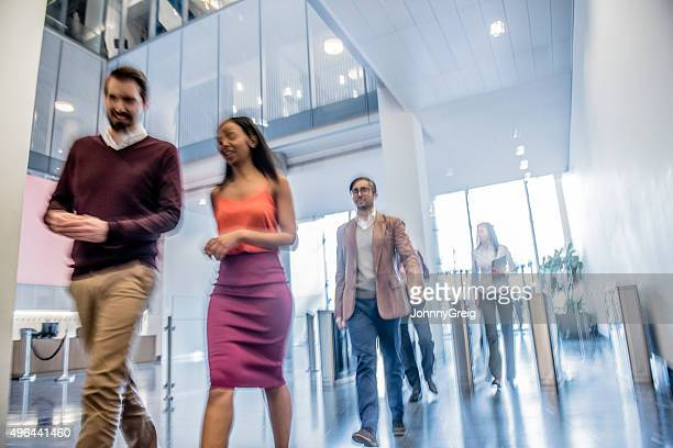 Business people walking in modern office, blurred motion
