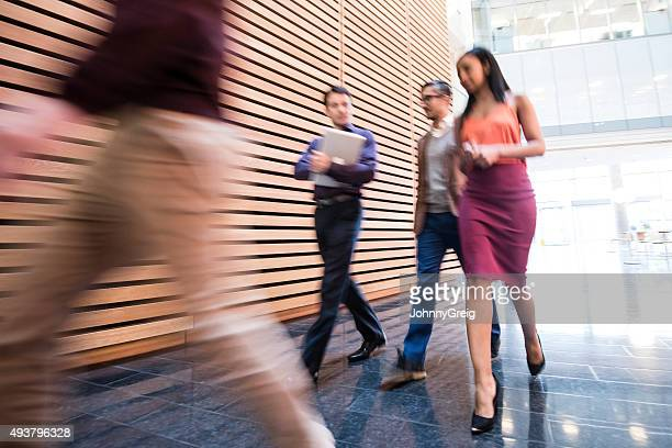 Business people walking in modern office with blurred motion