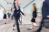 Blurred motion of businesswoman holding document and walking in office building.