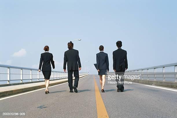 Business people walking on bridge, rear view